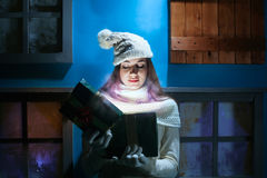 Young woman opens her gift Christmas in a magical house Royalty Free Stock Image