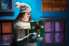 Young woman opens her gift Christmas in a magical house Royalty Free Stock Photo