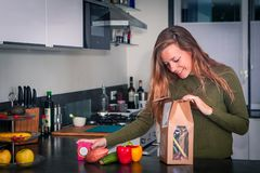 Young woman opens a package of fresh ingredients to make a healthy dinner royalty free stock photos