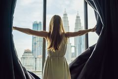 Young woman opens the window curtains and looks at the skyscrape. Rs in the big city Stock Image