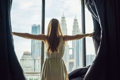 Young woman opens the window curtains and looks at the skyscrapers in the big city.  Stock Photo