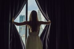 Young woman opens the window curtains and looks at the skyscrapers in the big city.  Royalty Free Stock Photos