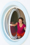 Young Woman Opens Window Made As Porthole Royalty Free Stock Images