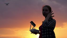 Young woman operates a panel to control a drone at sunset. An impressive view of a young woman who smiles and operates a panel with a screen to control a flying stock video footage
