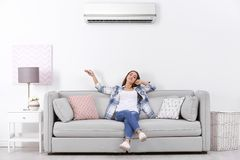 Young woman operating air conditioner while sitting royalty free stock photo