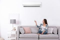 Young woman operating conditioner while sitting on sofa at home. Young woman operating air conditioner while sitting on sofa at home stock photo