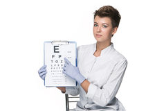Young woman ophthalmologist with eye chart Royalty Free Stock Images