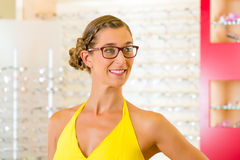 Young woman at optician with glasses Stock Images