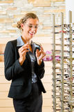 Young woman at optician with glasses stock image