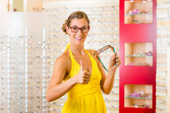 Young woman at optician with glasses Stock Photos