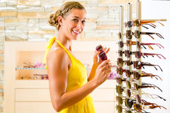 Young woman at optician shopping sunglasses Royalty Free Stock Photography