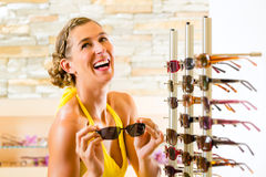 Young woman at optician shopping sunglasses. Young woman at optician with glasses, she is customer to the shop and buying some sunglasses royalty free stock images