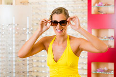 Young woman at optician with sunglasses Royalty Free Stock Photos