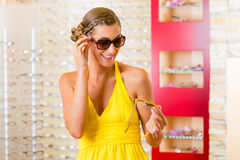 Young woman at optician with sunglasses Stock Image