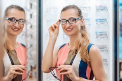 Young woman in optometrists store checking her looks in mirror royalty free stock photo