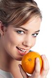 Young woman with orange. Portrait of pretty smiling young blond woman holding an orange; isolated on white Stock Photography