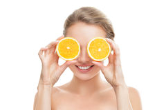 Young woman with orange in her Royalty Free Stock Photos