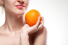 Young woman with orange isolated on white Stock Images