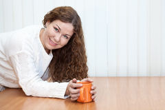Young woman with orange mug in hands looking at camera Stock Photography