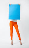 Young woman in orange pants holding blank blue placard hiding b Royalty Free Stock Images