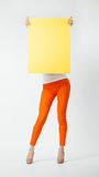 Young woman in orange pants holding blank yellow placard hiding. Behind it, full length portrait on neutral background Royalty Free Stock Photography