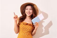 A young woman in a orange polka dots dress with a straw hat on her head is holding a passport and plane tickets.  stock photo