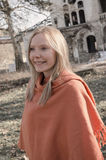 Young woman in orange poncho Stock Images