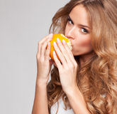Young woman with orange Stock Images