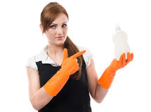 Young woman in orange rubber gloves. Pointing on dishwashing liquid bottle - isolated on white background Royalty Free Stock Photo