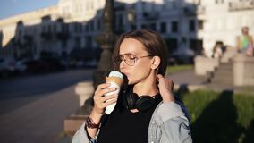 Young woman in orange shirt enjoying soft vanilla ice cream in waffle cone outdoors in slow motion. Female eating an ice. Cream on street alone, sitting on a stock video footage