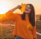 Young woman in a orange sweater with with yellow leaves, outdoor portrait in soft sunny daylight. Autumn. Sunset. Cozy royalty free stock photos