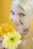 A Young Woman With An Orange And A Yellow Flower Stock Image