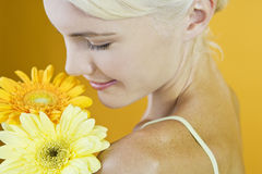 A Young Woman With An Orange And A Yellow Flower Royalty Free Stock Image