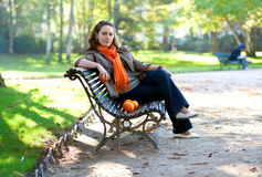 Young woman with oranges in park at spring or fall Stock Images