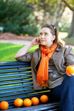 Young woman with oranges in park at spring or fall Stock Photo