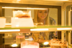 Young woman ordering in a coffee shop. A beautiful young woman ordering from a nice girl at the bar in a coffee shopr Royalty Free Stock Photography