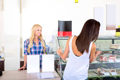 Young woman ordering in a coffee shop. A beautiful young women ordering from a nice girl at the bar in a coffee shopr Stock Photo