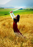 Young woman with ornamental dress and sword in hand  standing on a wheat field with sunset. Natural background. Royalty Free Stock Photos