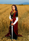 Young woman with ornamental dress and sword in hand  standing on a wheat field with sunset. Natural background.. Royalty Free Stock Image