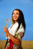 Young woman with ornamental dress and white fur standing on a wheat field with sunset. Holding bouquet. Stock Images