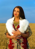 Young woman with ornamental dress and white fur standing on a wheat field with sunset. Natural background.. Royalty Free Stock Images