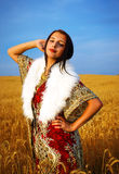 Young woman with ornamental dress and white fur standing on a wheat field with sunset. Natural background.. Royalty Free Stock Photo