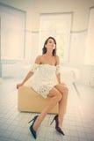 Young woman on ottoman Stock Photos