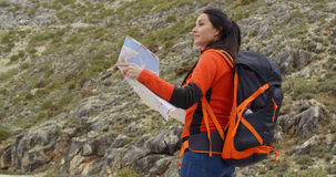 Young woman out hiking checking a map Stock Images