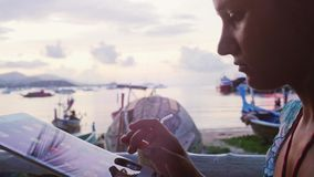 Young woman in outdoor cafe on the shore at sunset uses tablet computer and having drink. 3840x2160. 4k stock video footage