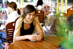 Young woman at outdoor coffee shop. Smiling Stock Images