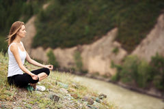 Young Woman Outdoor Meditation. Sitting on the Mountain. Stock Photo