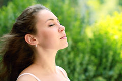 Young woman outdoor. Portrait of a beautiful brown-haired young woman outdoor showing her face to the wind Royalty Free Stock Images