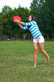 Young woman outdoor tossing a frisbee Stock Photos