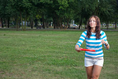 Young woman outdoor tossing a frisbee Stock Images
